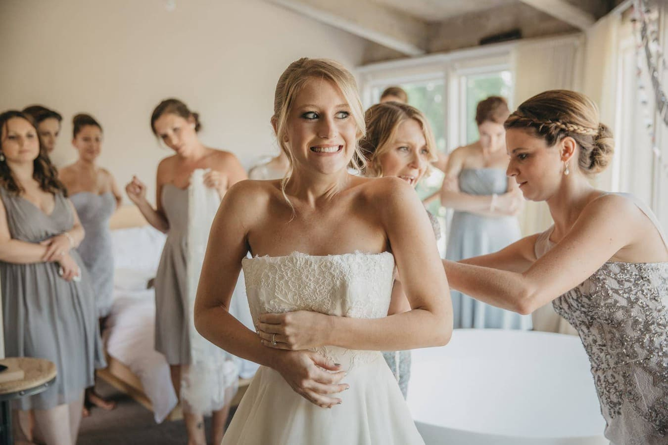 Bride with nervous smile has dress zipped up at The Roundhouse, Hudson Valley