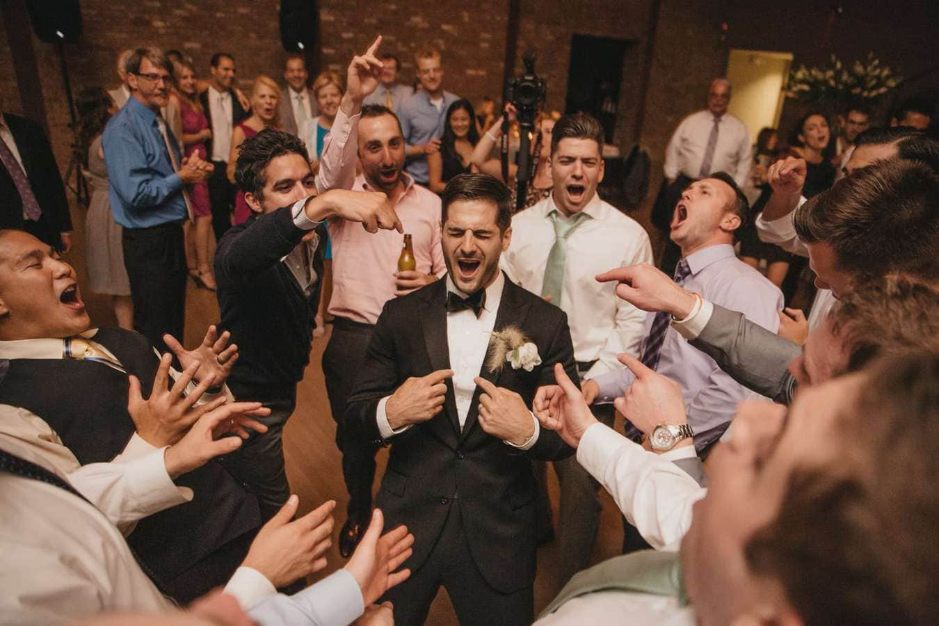 Friends of groom stand around him in a circle and sing enthusiastically during wedding reception