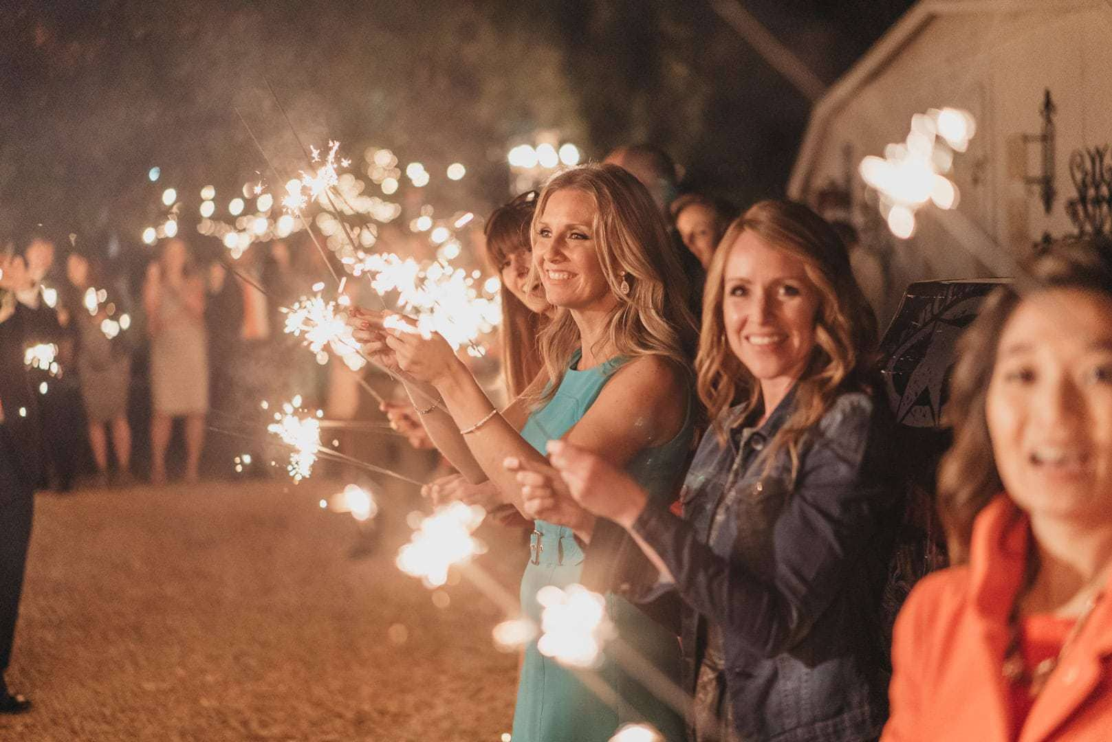 Guests hold sparklers out after wedding reception