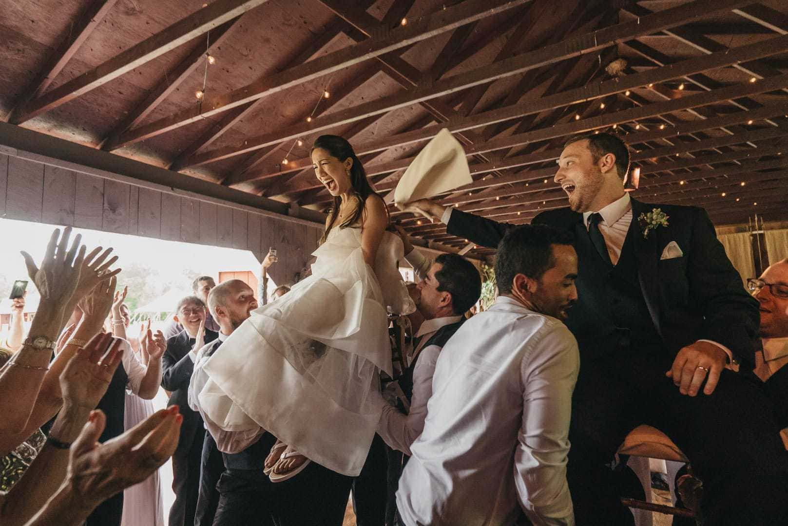 Bride and groom are lifted up on chairs during hora at wedding reception, groom looking excited and bride smiling widely but nervously.