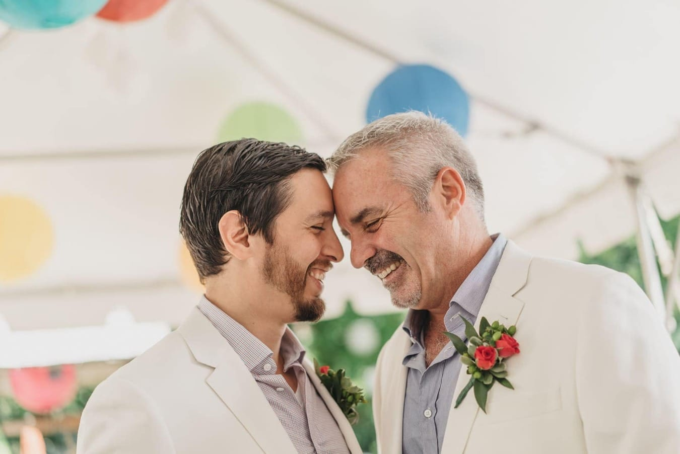 Gay couple smiles and puts heads together during wedding reception