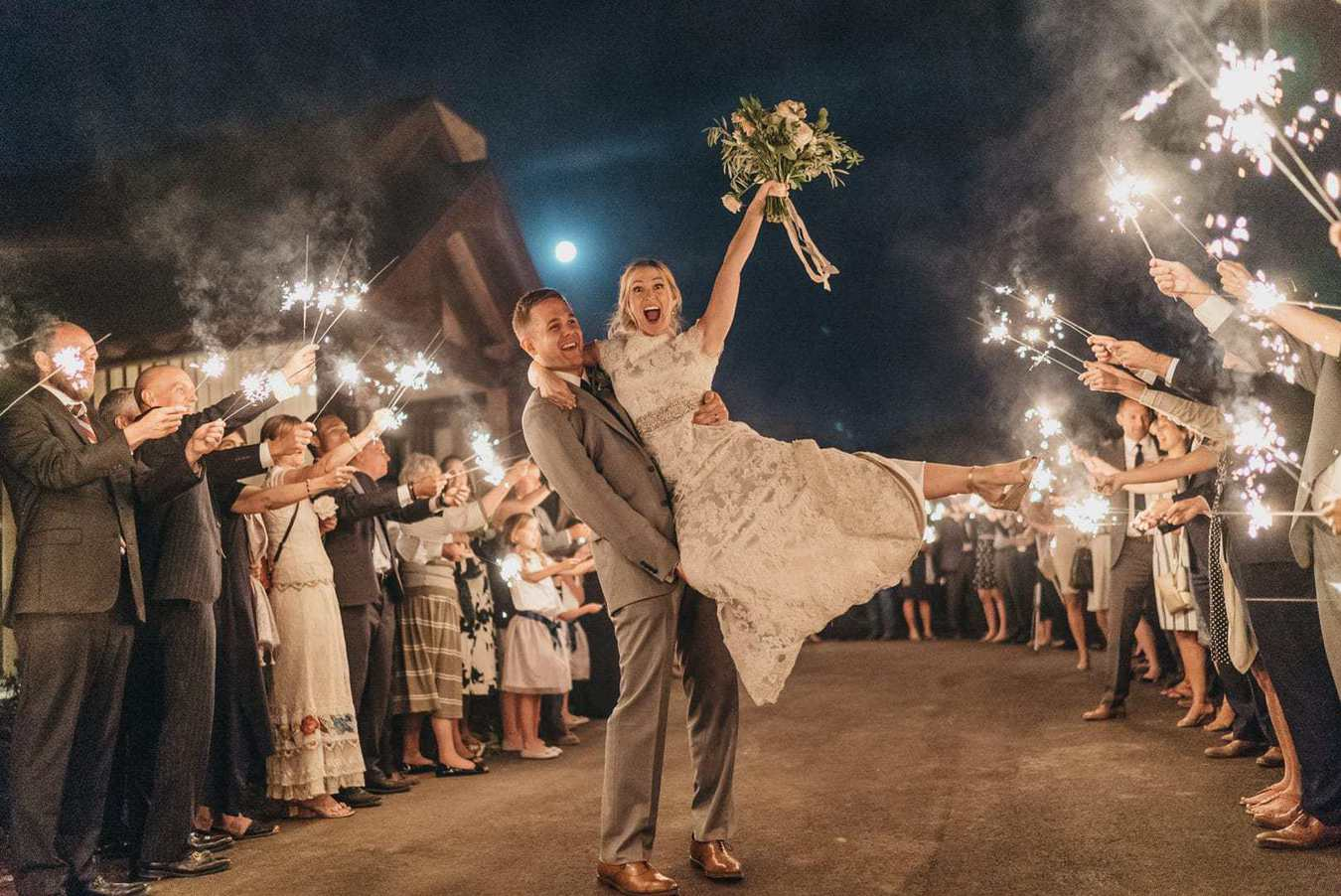 Groom holds bride up as she jumps up and smiles while sparklers are lit around them at their wedding reception.