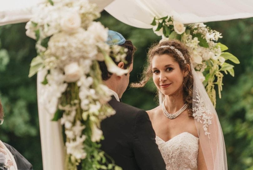 Bride looks away and smiles during Jewish wedding in Hudson Valley
