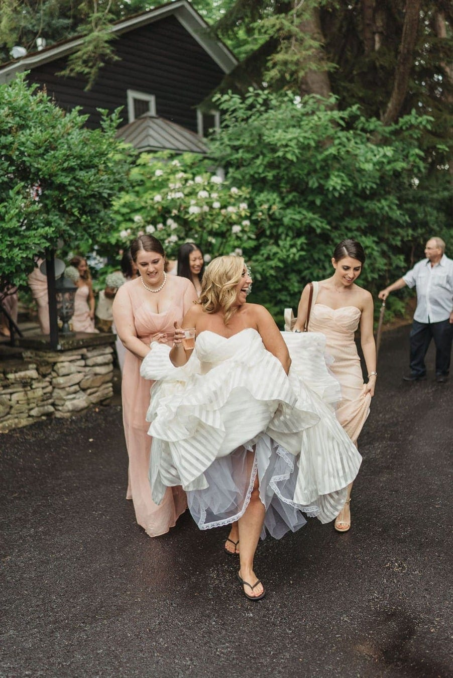 Bride smiles as she and bridesmaids lift up her wedding dress dress