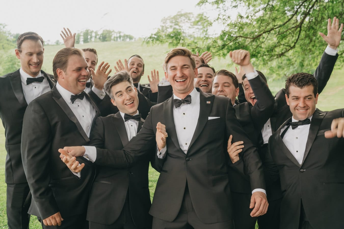 Groomsmen crowd excitedly around groom, smiling and putting their hands up at Catskill wedding venue.