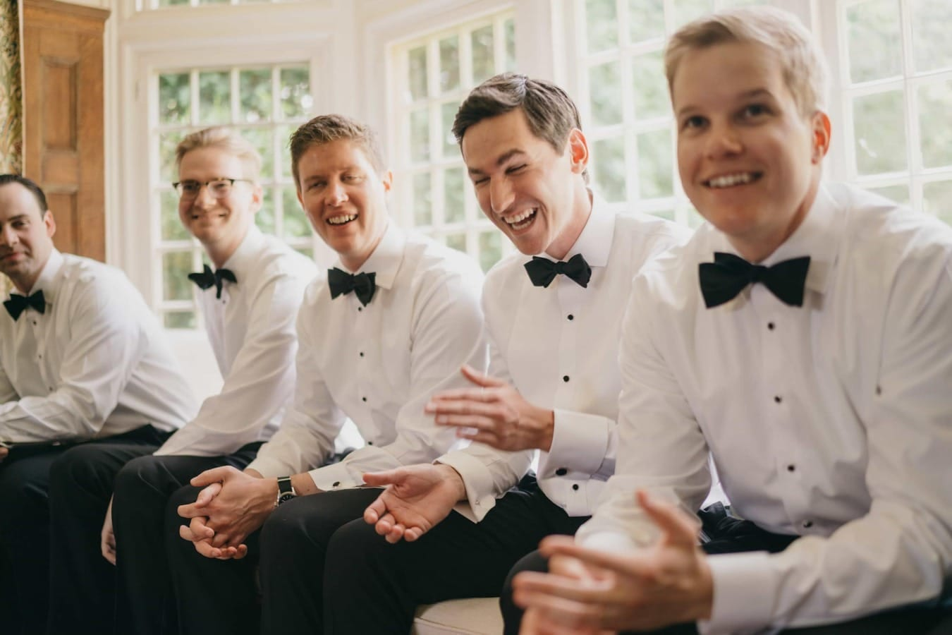 Groomsmen sit in window seat smiling, one laughing, before wedding ceremony.