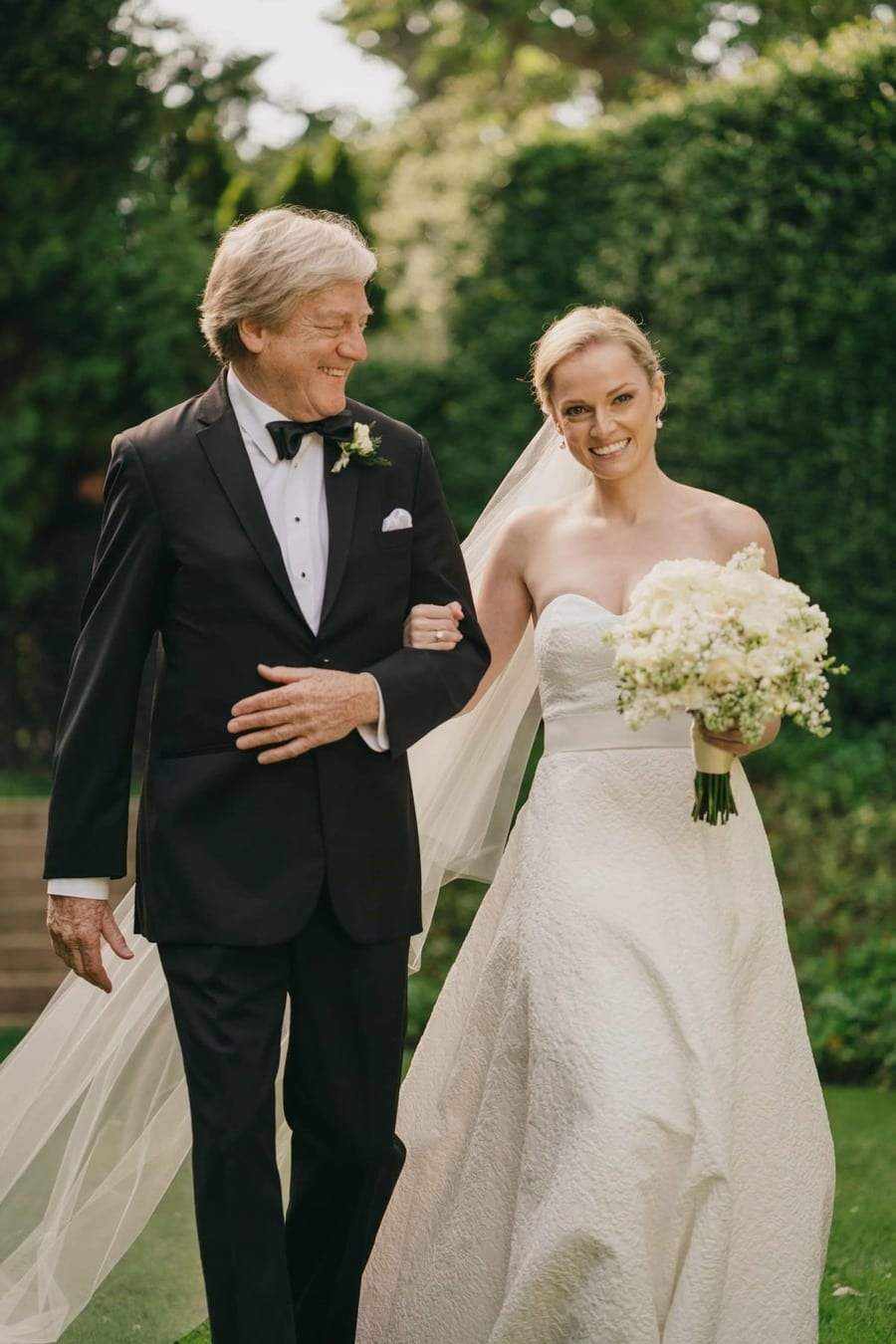 Bride and father walk down aisle during wedding ceremony in the Catskills