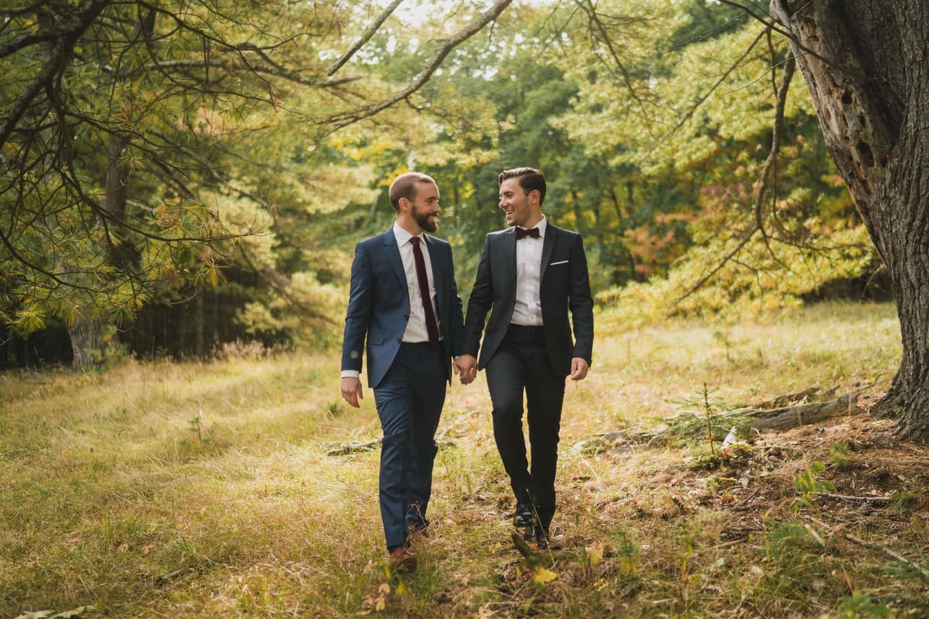 Gay couple hold hands and walk together in Catskills.