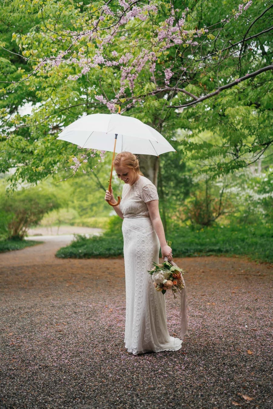 Bride in wedding dress smiles and looks at ground, holding bouquet and white umbrella.