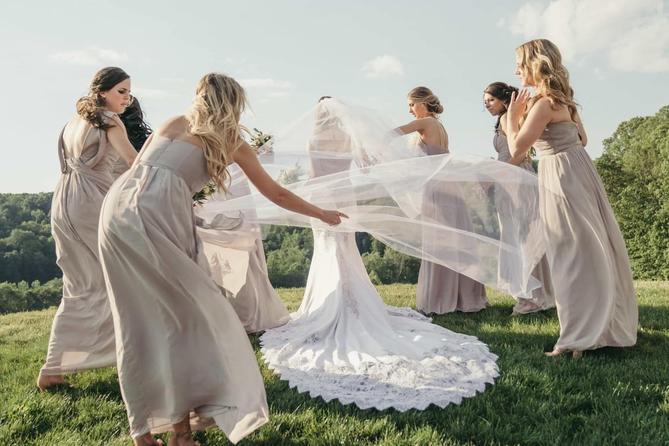 Bridesmaids circle around bride and one holds bride's veil as the wind blows it.