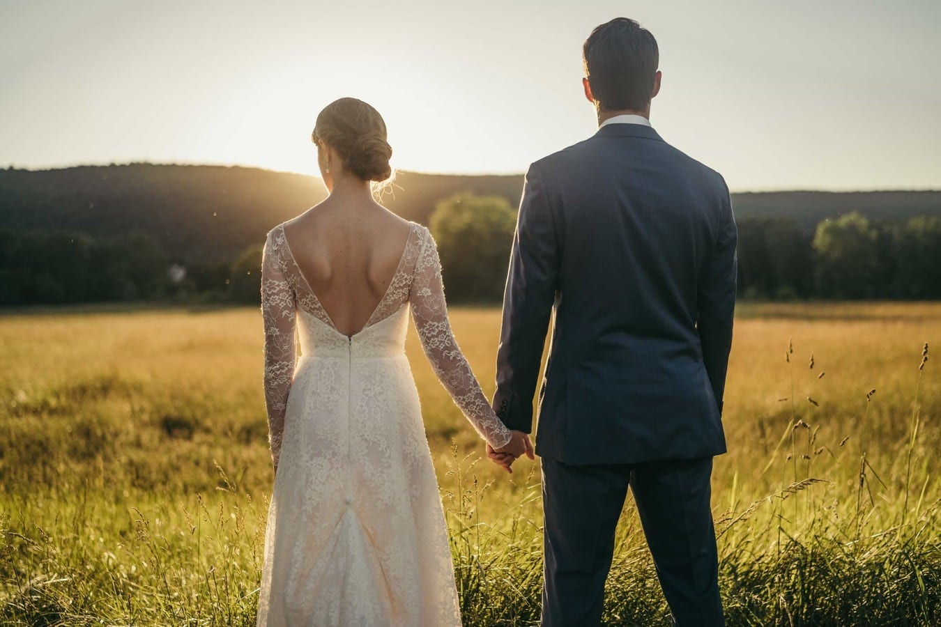 Bride and groom stand in field holding hands and sunset glows around bride's head in Catskills.