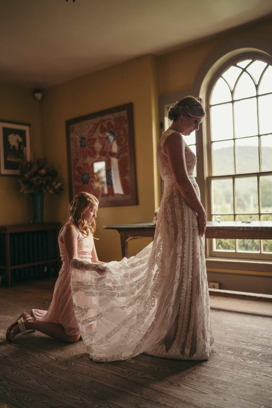 Flower girl fixes bride's dress as light from window comes into room and shines through lace dress before wedding ceremony.