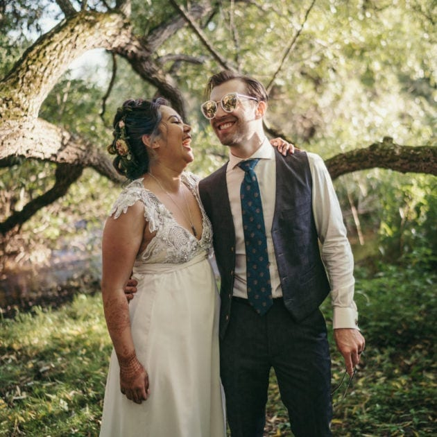 Bride and groom stand in Catskill forest, laughing as groom wears bride's sunglasses.