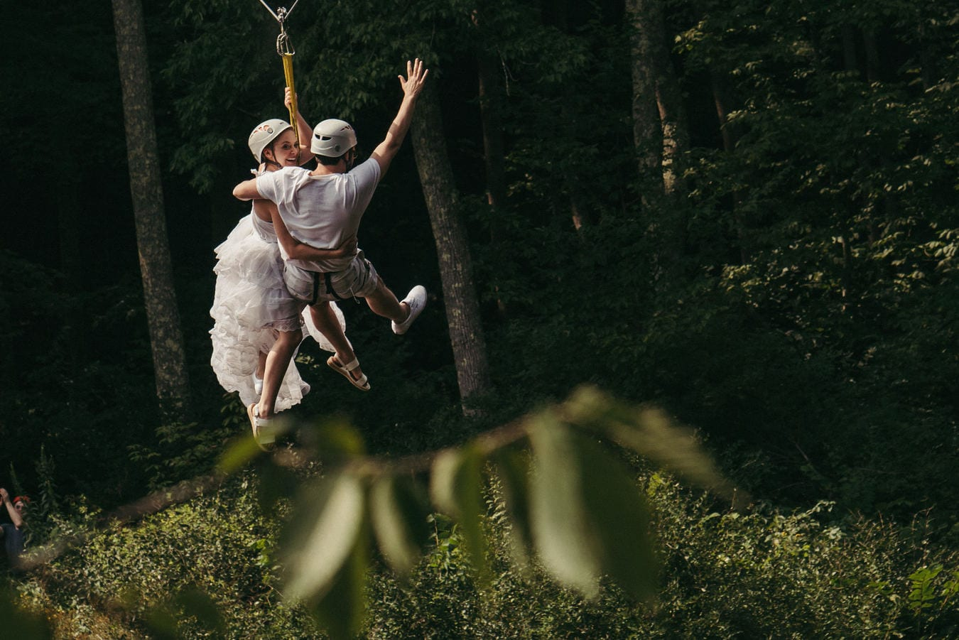 Bride and groom ride zip line through Catskill forest after wedding ceremony.