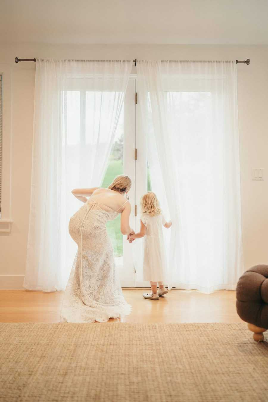 Bride and flower girl pull back curtains to look through glass door before wedding ceremony.