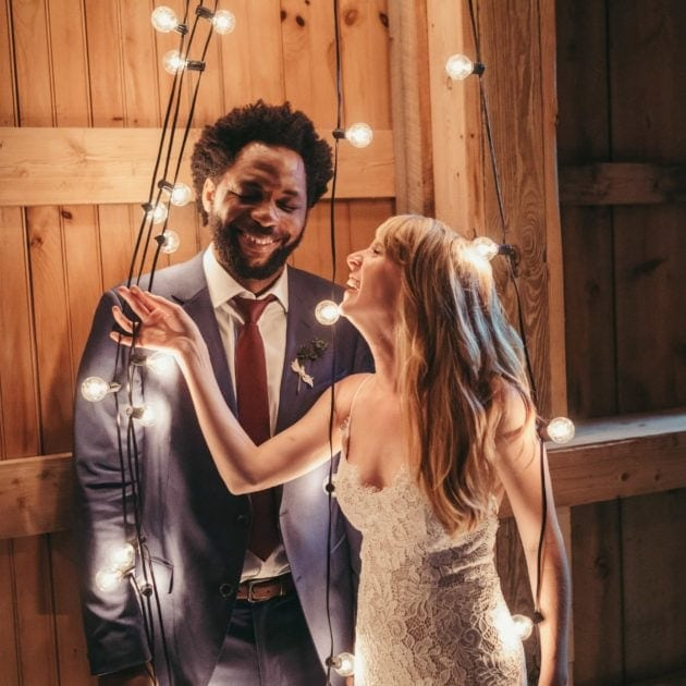 Bride and groom stand together in string lights and laugh, at Catskill wedding venue.
