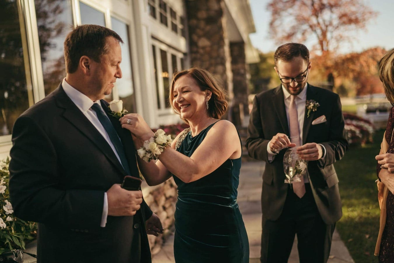 Mother pins boutonniere on her husband before wedding ceremony.