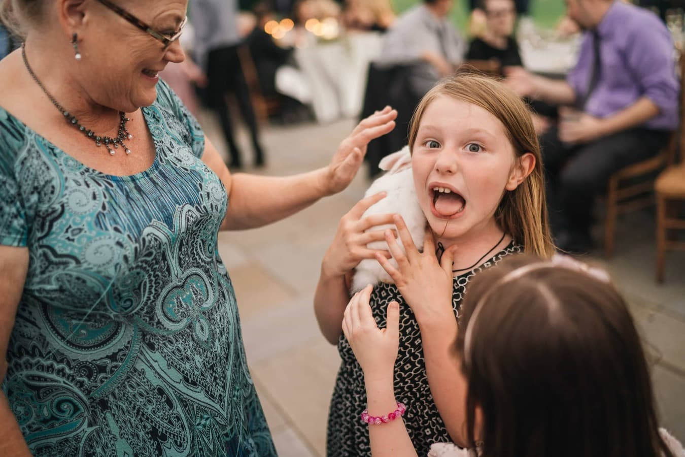 Little girl holding a white rabbit on her shoulder makes funny face by sticking out tongue during wedding reception in Hudson Valley.