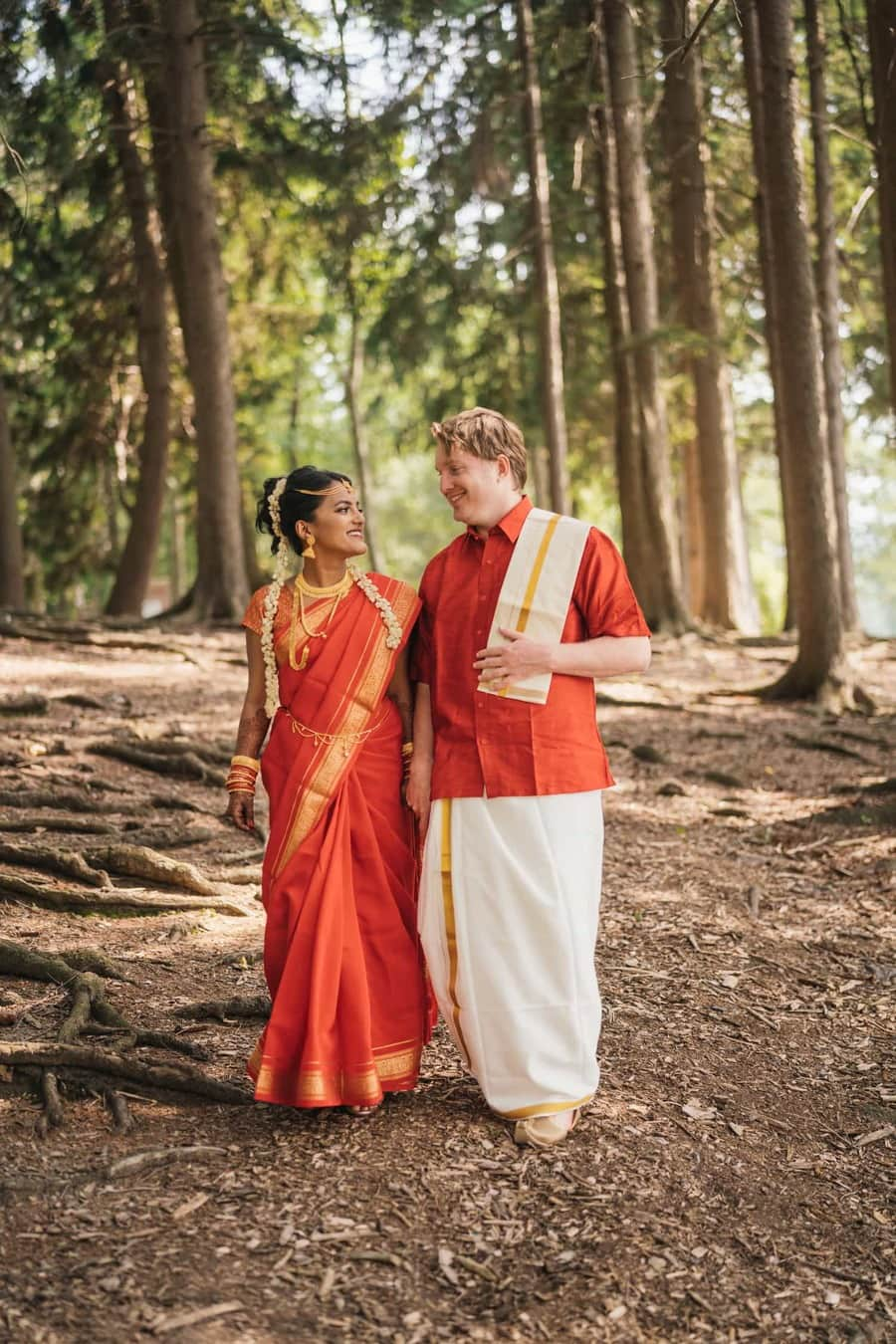 Indian Bride and groom holds hands and walk together through Hudson Valley forest.