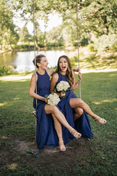 Bridesmaids sit and laugh on swing, Hudson Valley pond and trees in background