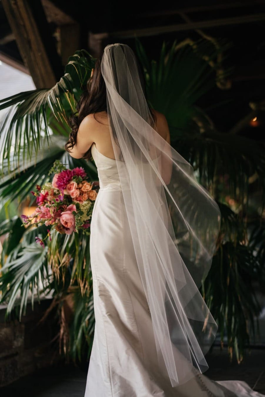 Bride in dress and long dress turns back to camera while standing in palm plant.