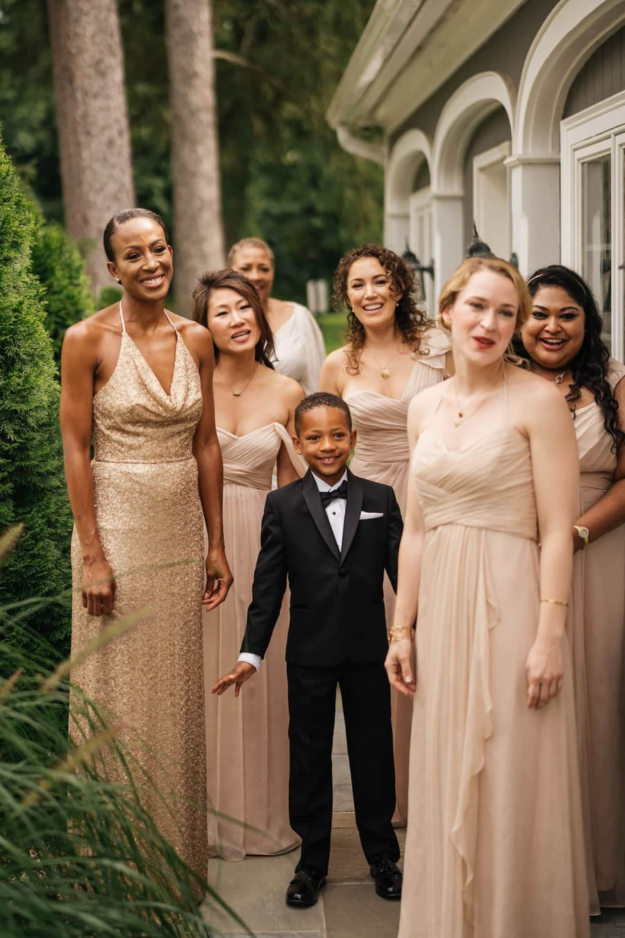 Bridesmaids and nephew of bride admire bride as she shows them her wedding dress.