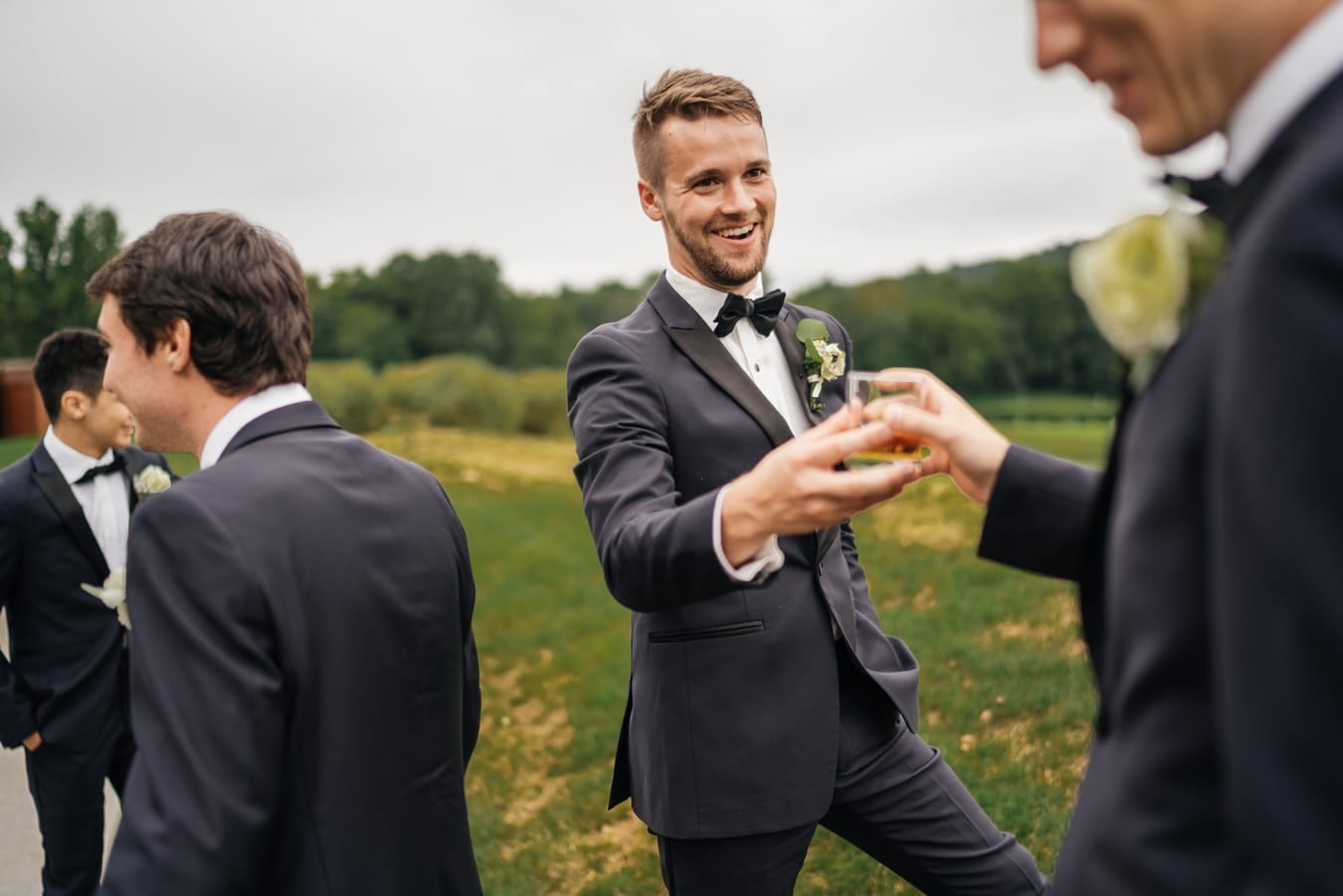 Groomsman hands groom a drink during family portraits and groom smiles.