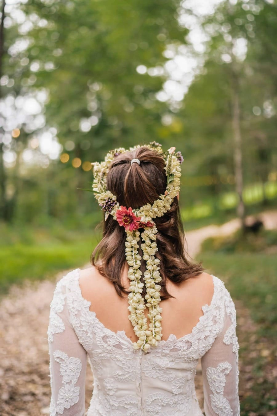Bride's hair is decorated with flower wreaths and is wearing lace dress for wedding in Catskills.
