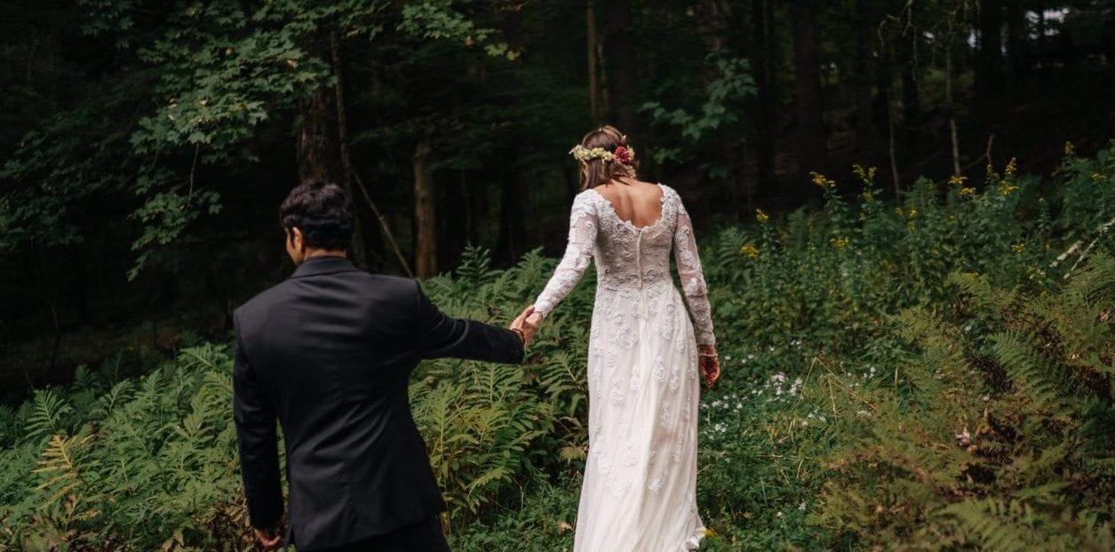 Bride in dress leads groom in black suit through Hudson Valley forest with ferns and trees.