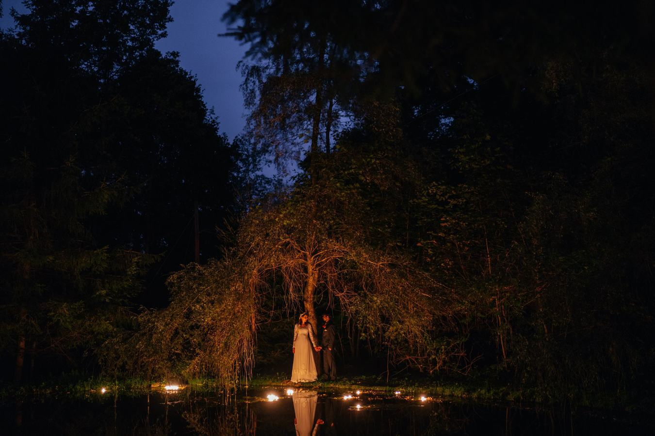 Bride and groom stand underneath tree by candle lit pond and hold hands at night at Catskill wedding venue.
