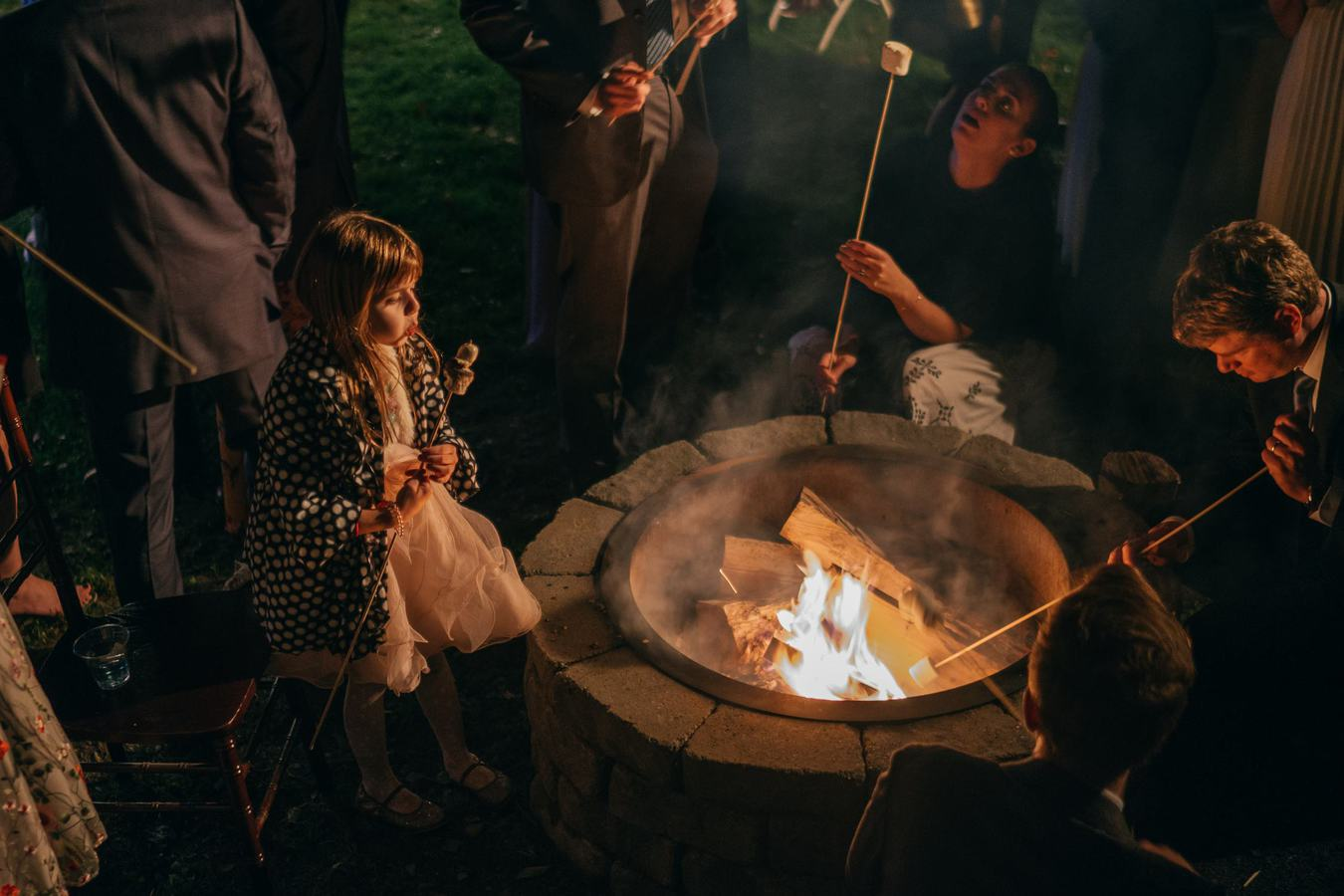 Wedding guests sit around fire pit to make s'mores, and a little girl blows on her marshmallow to cool it down after cooking it.