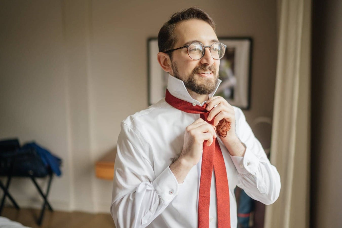 Groom ties red tie by window at Hudson Valley wedding venue.