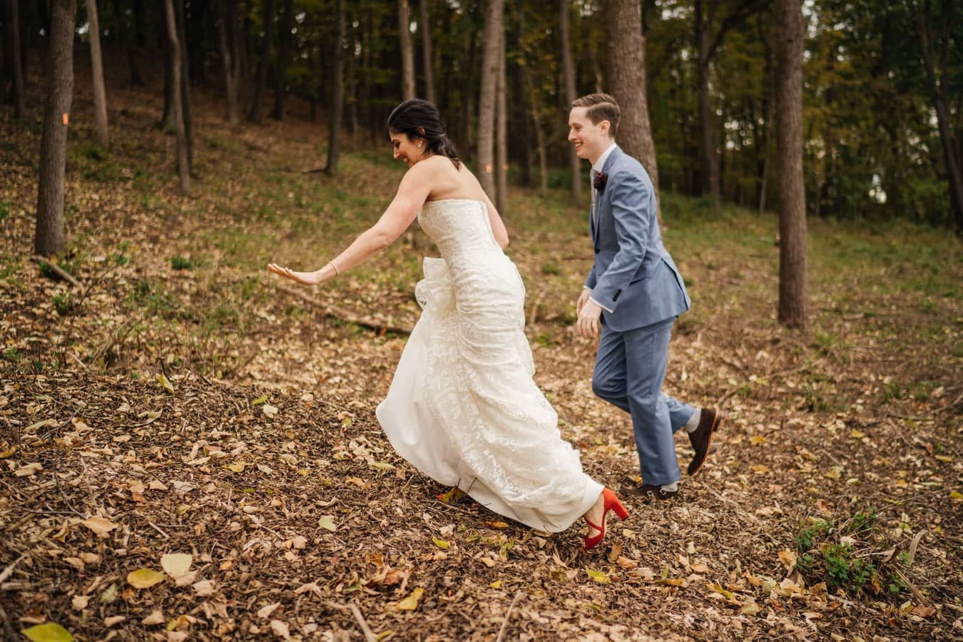 Bride and groom walk up fall hill excitedly together at Catskill wedding venue.