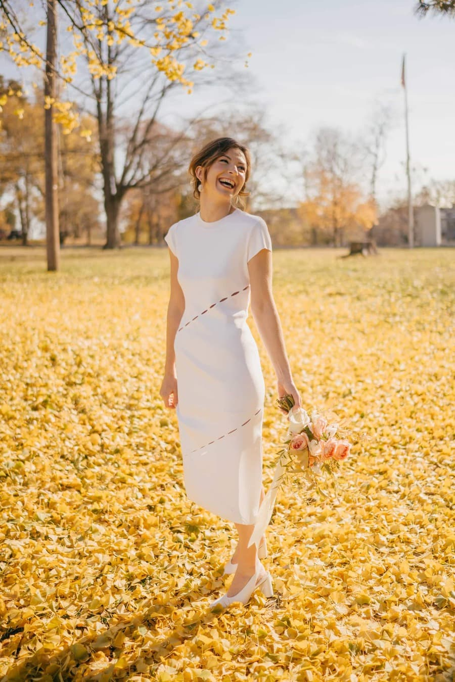 Bride in wedding dress and holding small bouquet by side smiles and laughs as she looks away from the camera while standing in fall leaves.