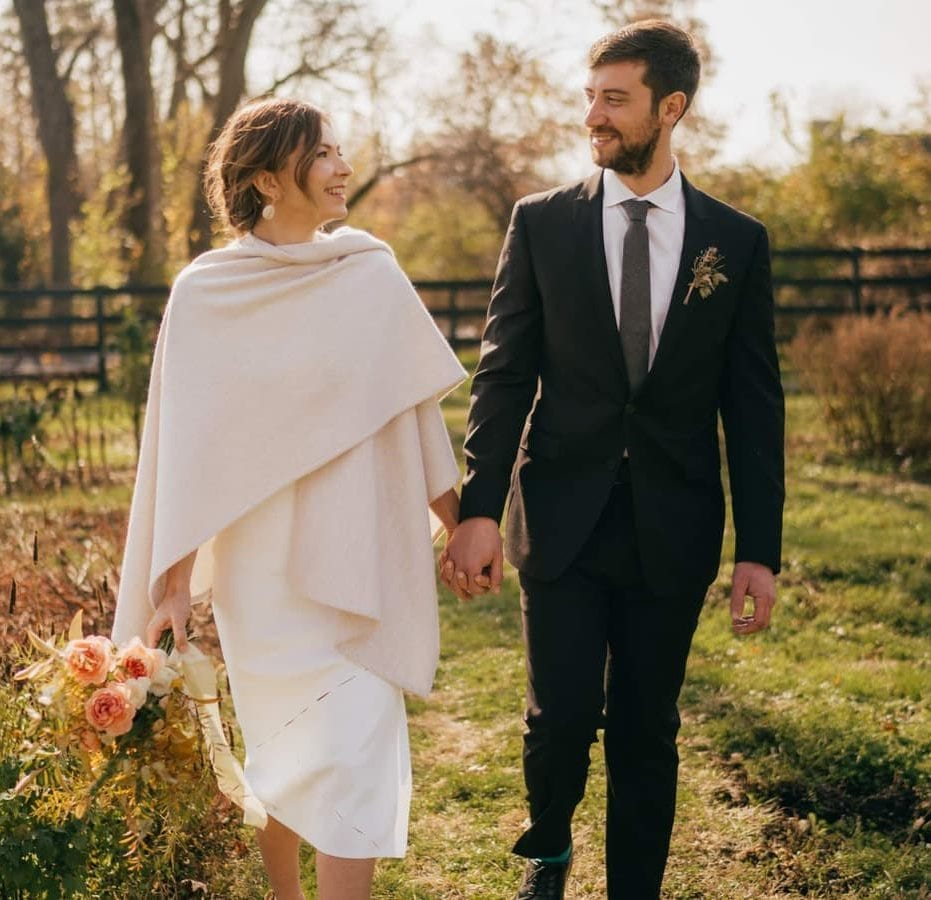 Bride and groom hold hands and walk together through farm wedding venue in Catskills.