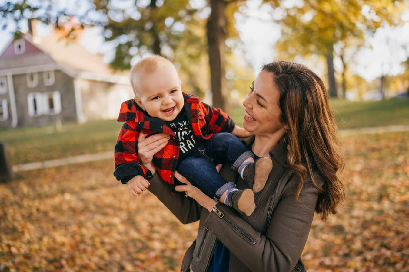Mom holds infant son as they both smile, standing in fall leaves in Hudson Valley