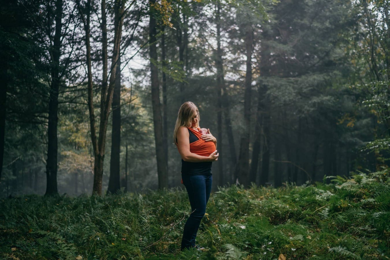 Mother looking young baby wrapped around chest stands in Catskill forest