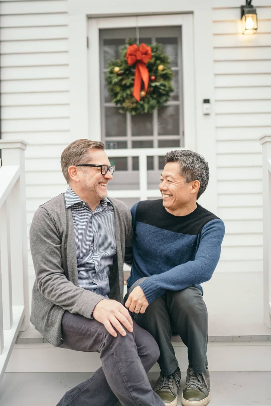 Gay couple sit on porch and smile at each other at Hudson Valley home.