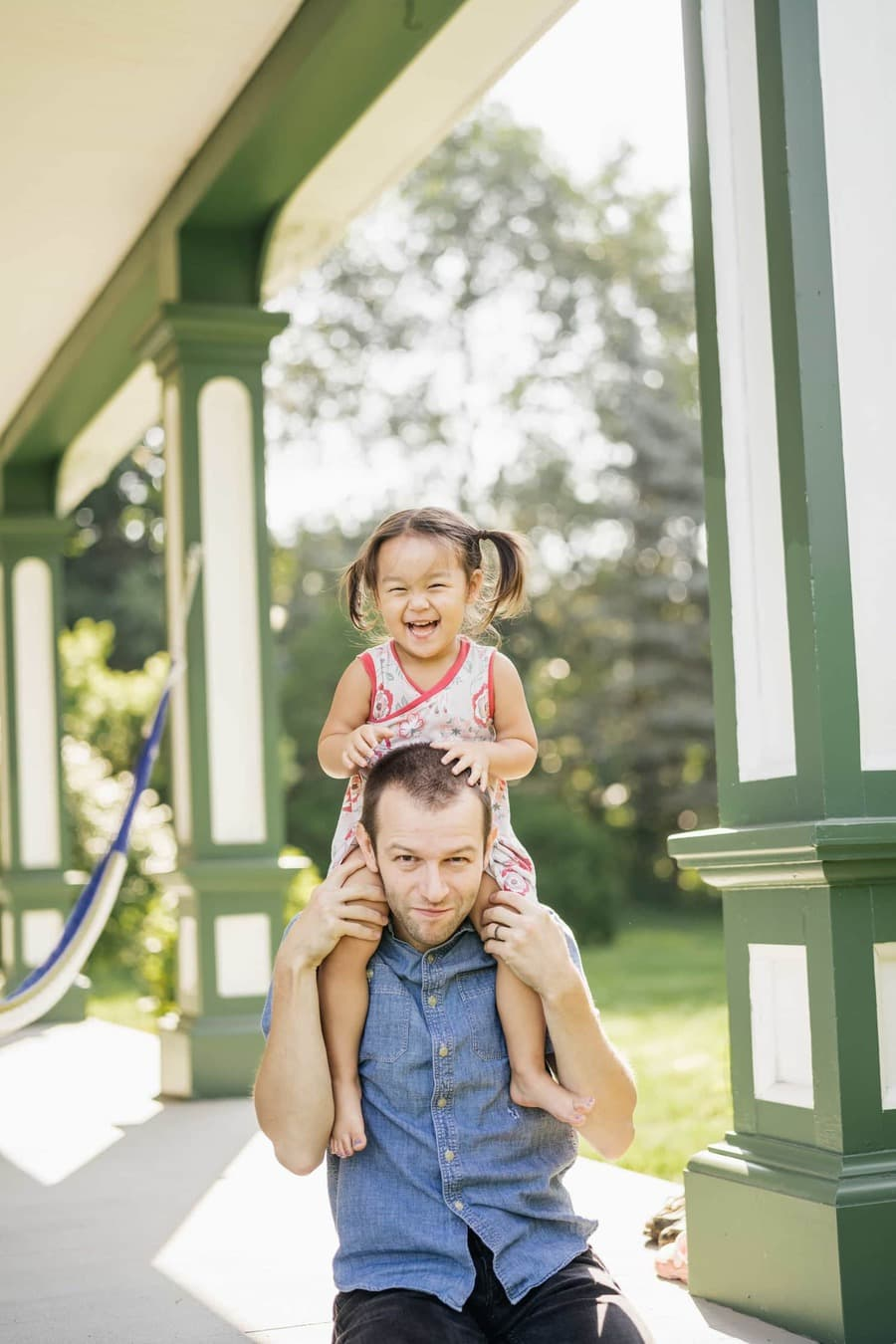 Young daughter sits on dad's shoulders as they sit on their Hudson Valley home's porch