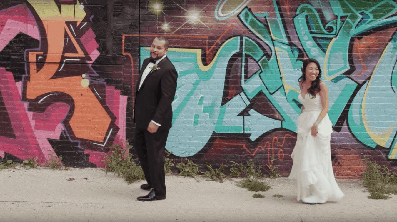 Bride and groom first look against vibrant graffiti background