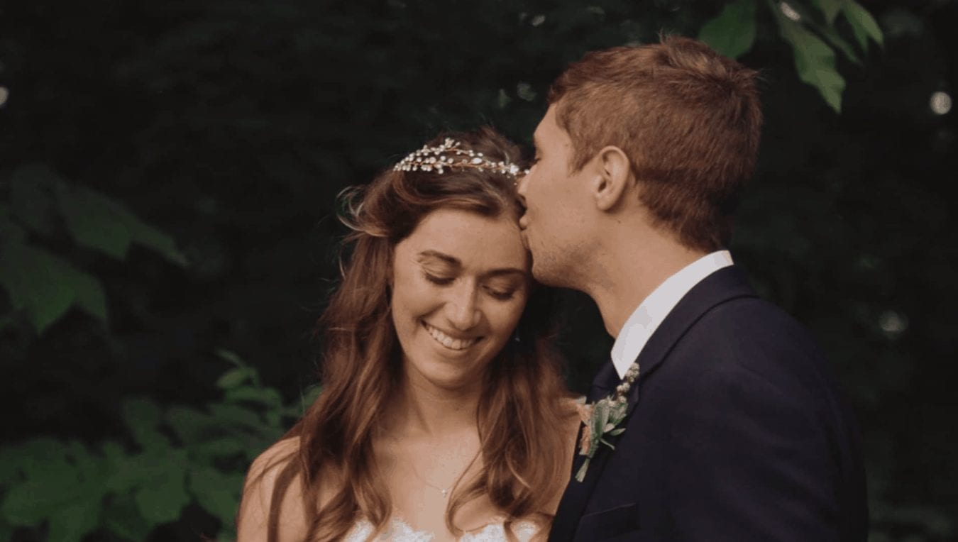 Groom kisses bride's forehead as she smiles in Hudson Valley forest.