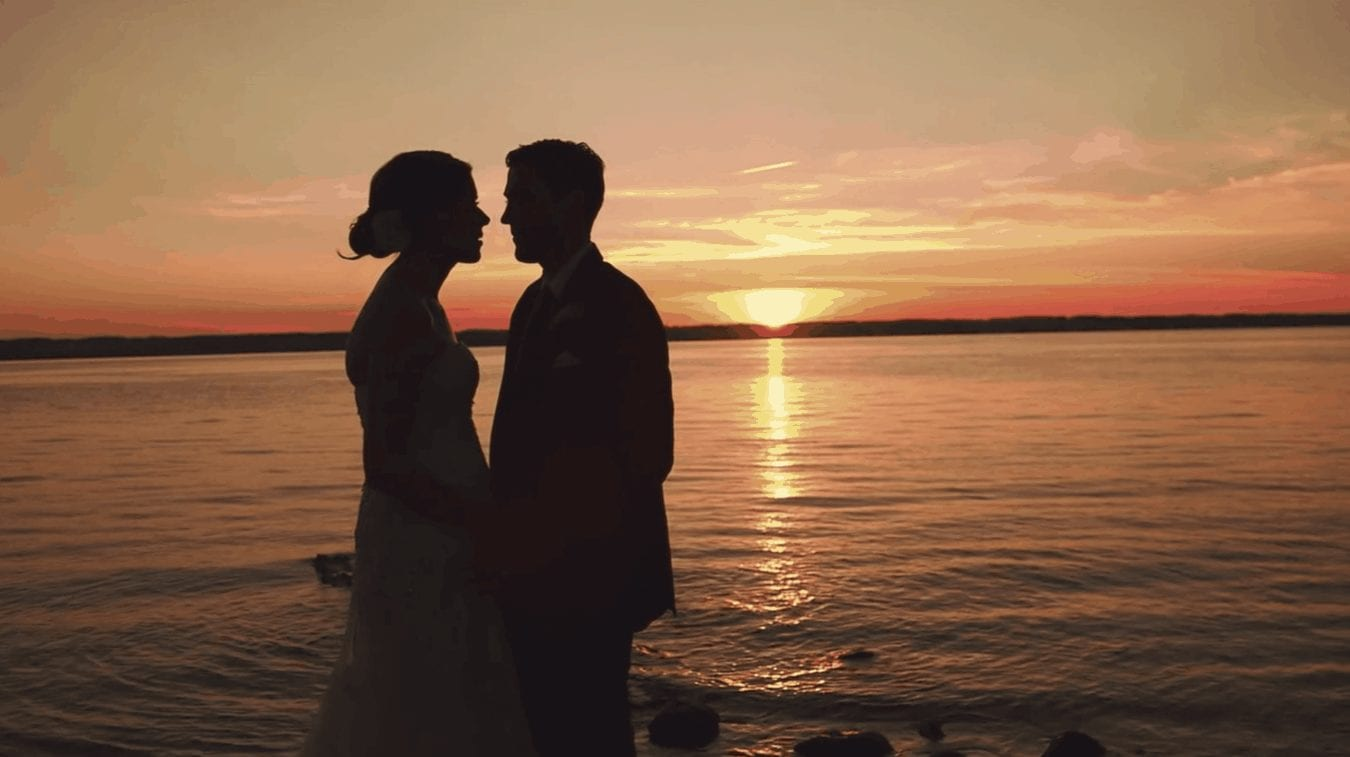 Bride and groom silhouette against sunset on lake.