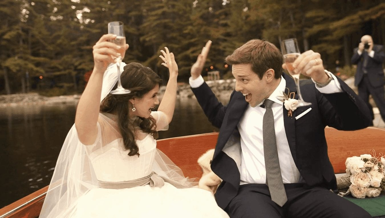 Bride and groom in boat smile at each other and throw their arms up in celebration.