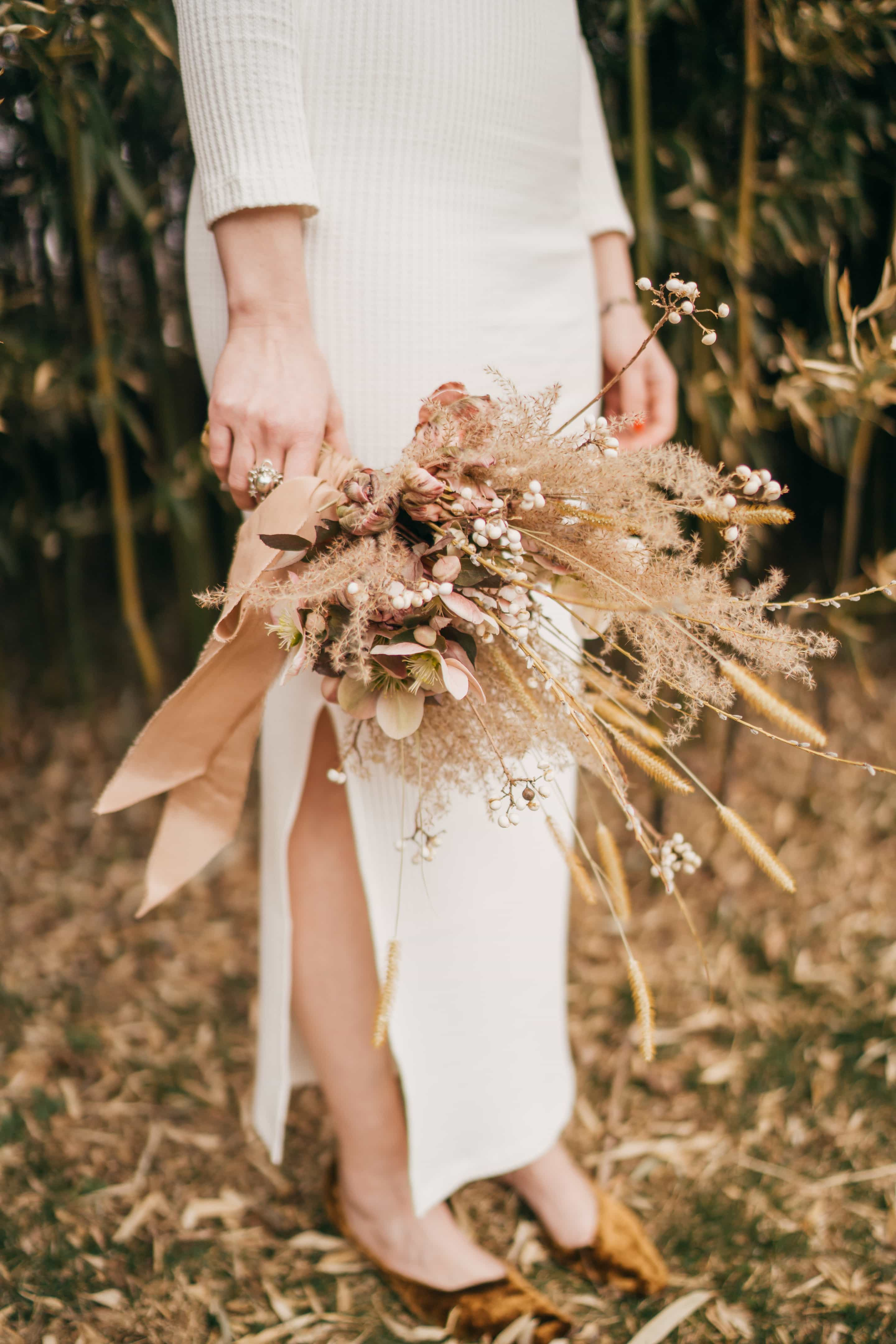 Bride holds dry brown grass and weeds bouquet.