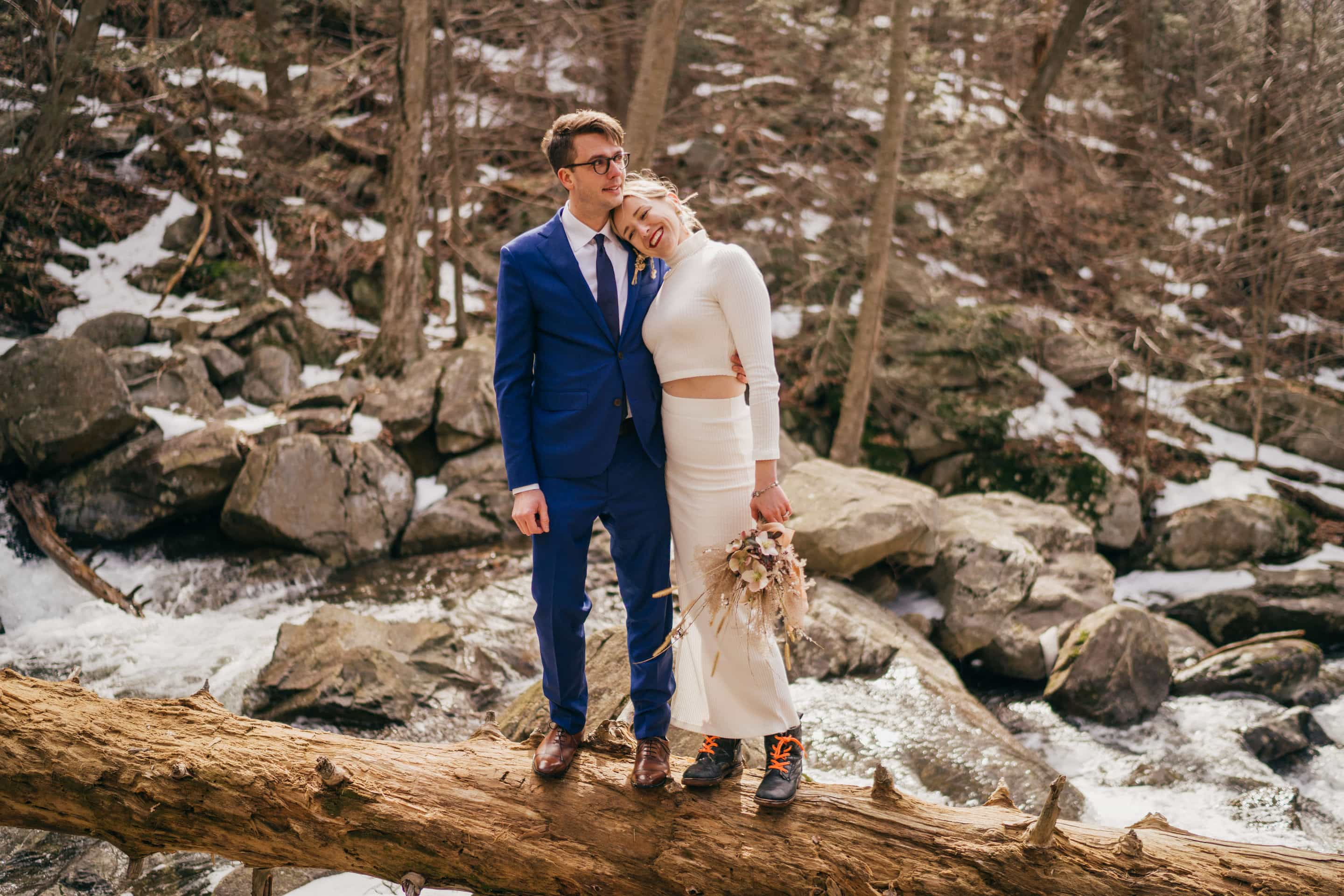 Bride in dress and hiking boots smiles and leans on groom's shoulder as he puts his arm around her waist, standing on a log over a river in winter Hudson Valley forest.