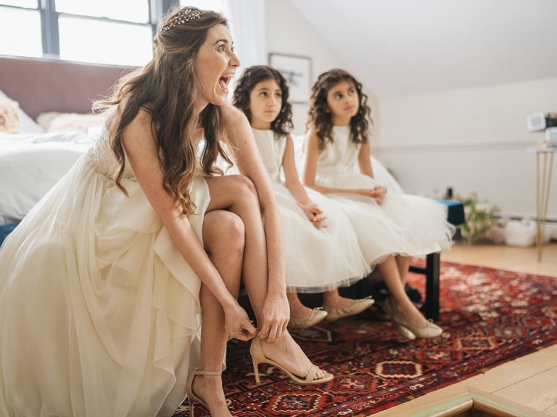 Bride sits with flower girls and puts on shoes before wedding ceremony.