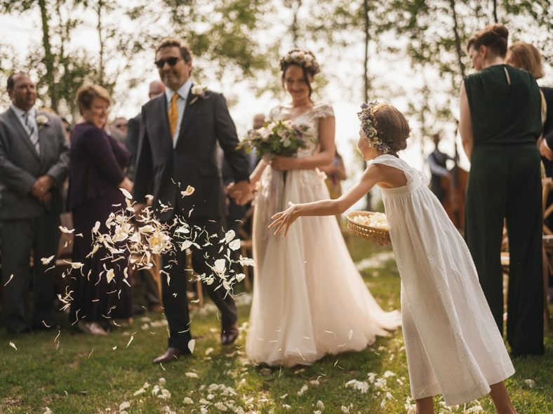 Flower girl throws handful of flowers in front of bride as she walks down aisle.