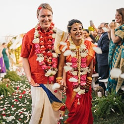 Bride and groom after Indian wedding ceremony walk down aisle after ceremony finishes.