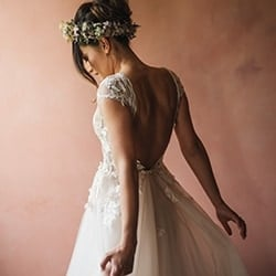Bride in wedding dress and flower crown turns back to camera as she flares out dress.