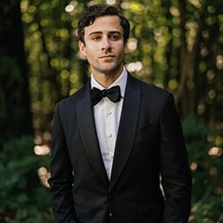 Groom in black suit and black bow tie looks away from camera seriously with Hudson Valley forest background.